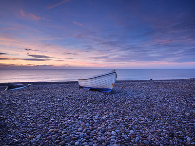 Photogenic fishing boat and dawn sky on the pebbled beach  at Budliegh Salterton, Devon, UK