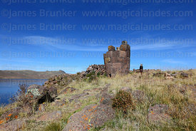 Tourist looking at cut stone Inca period chulpa / burial tower and Lake Umayo, Sillustani, Peru