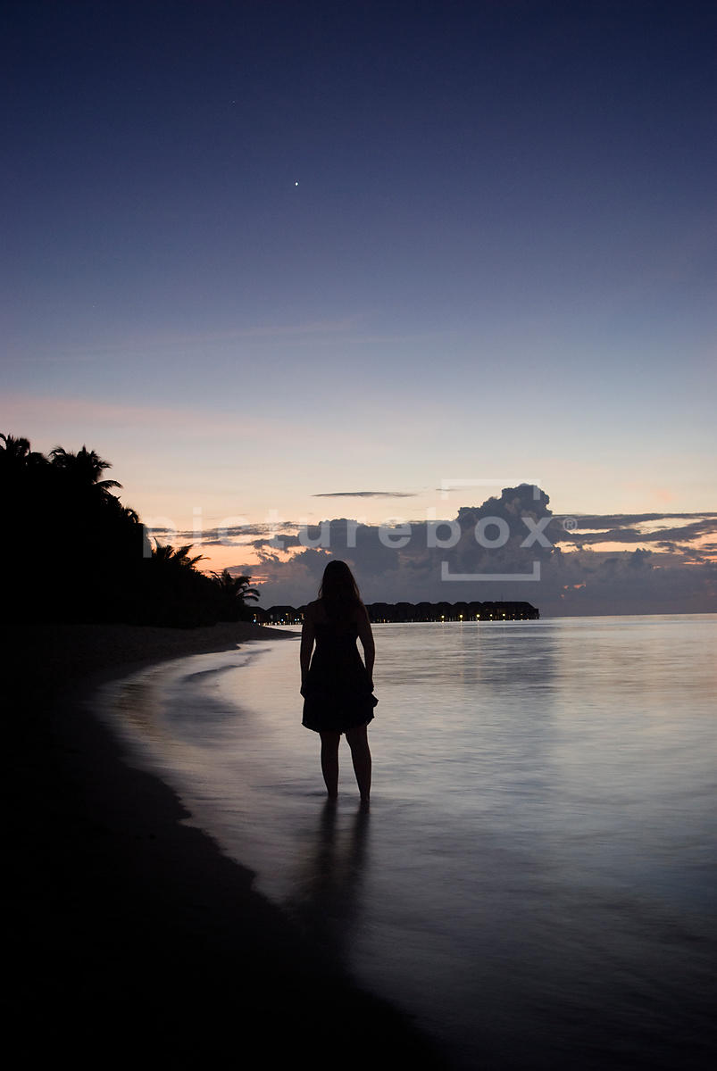 An atmospheric image of  a woman paddling in the sea, on a tropical beach, at sunset, in the Maldives.