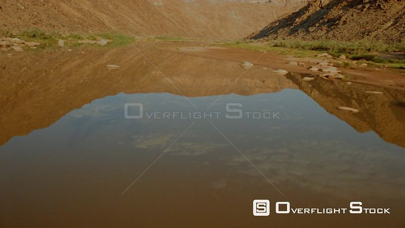 Aerial flying up river with green vegetation on riverbank and mountains and cloudy sky reflected in water Fish River Canyon N...
