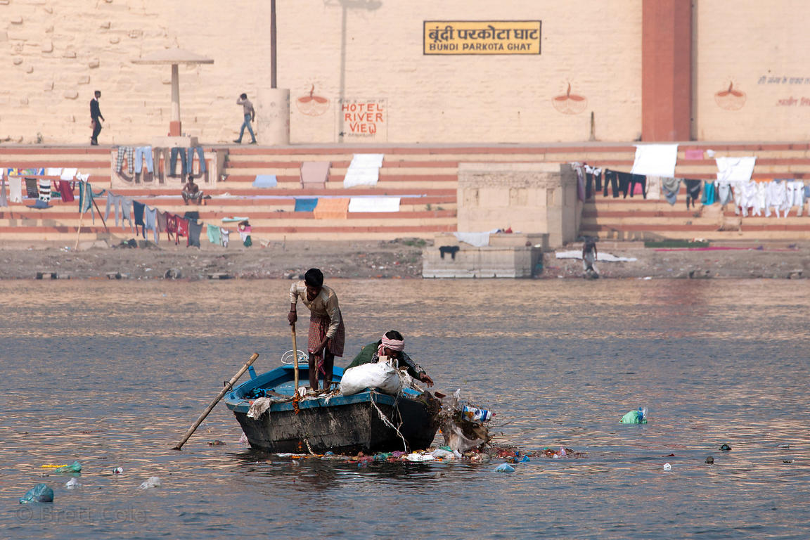 A garbage collection boat dumps boat loads of garbage into the Ganges River, Varanasi, India.