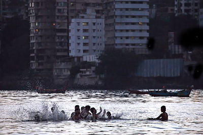 Swimmers in Back Bay in the Araban Sea at night, with Malabar Hill in the background. Mumbai, India.