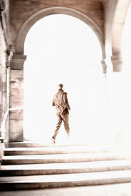 An atmospheric image of a man running up some steps and out into the sunlight, in Venice, Italy.