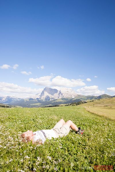 Adult man relaxing on meadow in the mountains