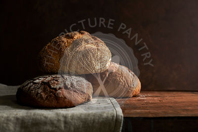 A variety of rustic bread loaves on a linen and a rich, wood surface.