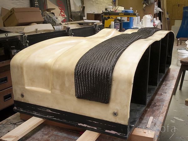 Moulding a crossbeam using tubular carbon fibre braid  formed on a foam blank