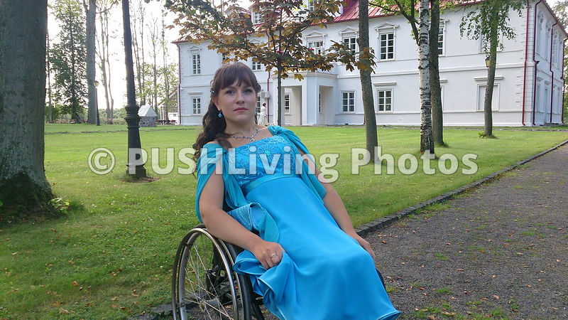 Woman in a wheelchair in an evening gown in the garden of a stately mansion