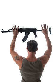 A man standing, surrendering, holding an AK-47 in the air.