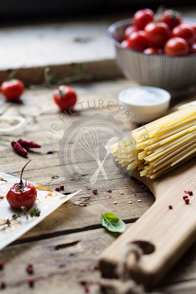 Food background. Spaghetti, tomatoes and hot pepper on wooden rustic table. Spaghetti in the making