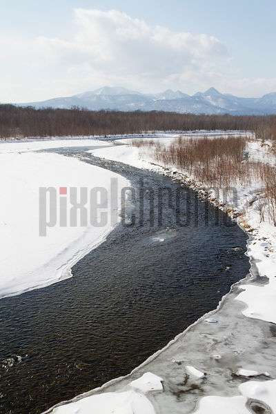 Stream through snow-covered landscape