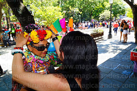 A woman gives her friend / comadre a crown of flowers during the Comadres festival, Tarija, Bolivia