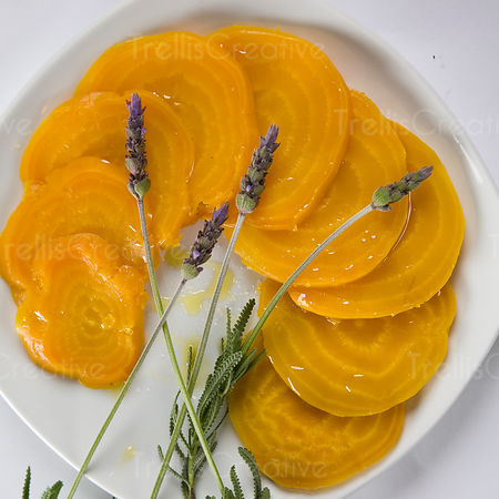 Sliced roasted golden yellow beets arranged on a white plate
