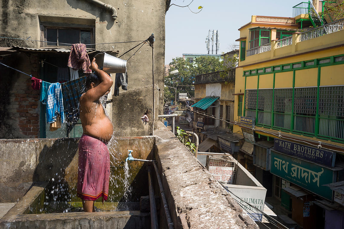 A waiter washes after his shift on the terrace of the Indian Coffee House, Kolkata