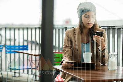 Young woman sitting at sidewalk cafe holding digital tablet while using smartphone