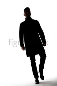 A Figurestock image of a mystery man, in silhouette, walking towards the camera – shot from low level.