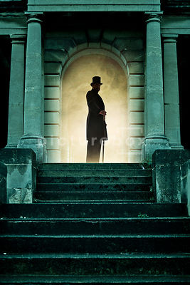 A Victorian man with a hat, coat and cane, at the top of some old stone steps.