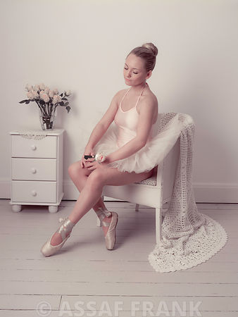 Cute young Ballerina sitting on a chair with rose