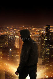 An atmospheric image of a lone mystery man standing on top of a tall building in New York, at night.