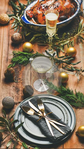 Roast chicken or turkey, plates, silverware, champagne and toy holiday decoration over rustic wooden background