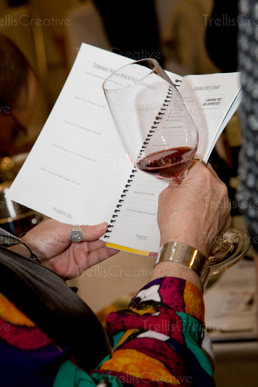 Older woman's hand holding glass of red wine and book
