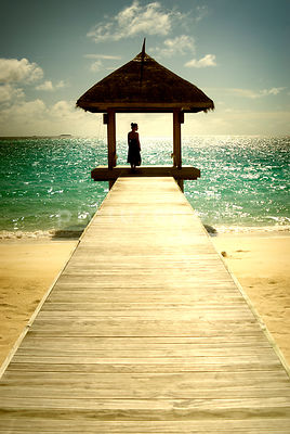An atmospheric image of a lone woman in a blue dress, standing at the end of a dock, on a tropical beach.