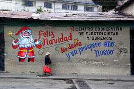 Man walking past Father Christmas mural on wall of the offices of an electricians and electrical workers cooperative, La Paz,...
