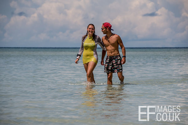 Couple Wading Through Shallow Water On A Tropical Beach