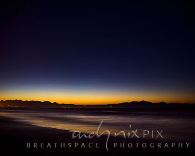 A couple of stars shine in a dark blue sky with the yellow light of dawn over mountains reflected in the waves breaking on a ...