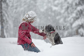 Dog and owner holding hands in snow
