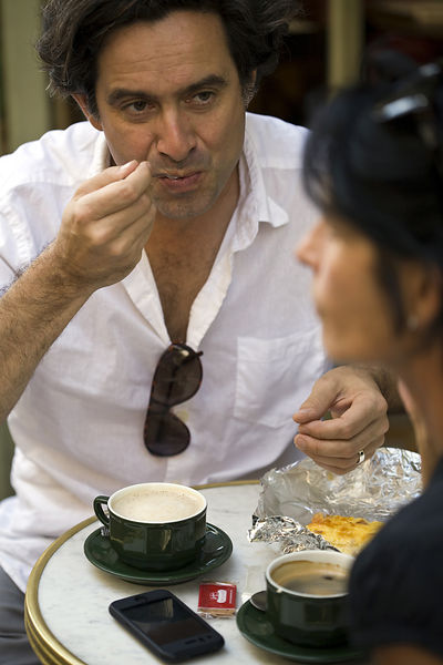 France - Paris - A man sits, talks and spoons sugar into coffee at a cafe on the Rue Mouffetard