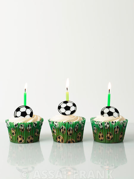 Three football cupcakes with birthday candles