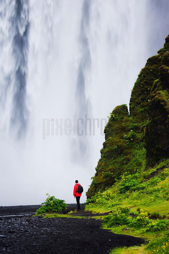 Person Looking at Skogafoss Waterfall, Iceland