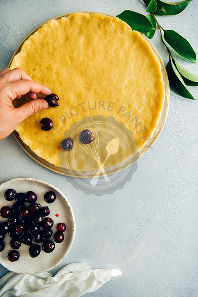 A woman placing pitted cherries on a pie dough and pitted cherries on a white plate on the side photographed from top view. G...