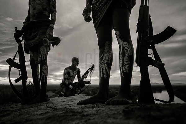 Kara Men Standing on the Bank of the Omo River with their AK-47s at Dusk