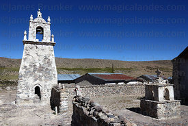 Guallatiri village church bell tower and cairn with cross in entrance courtyard , Las Vicuñas National Reserve , Region XV , ...