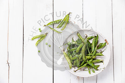 Fresh green pea in pods on white wooden background