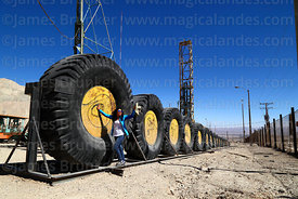 Huge mining dump truck tyres and blasthole drill (in background) on display near Chuquicamata mine, Region II, Chile