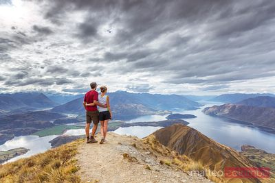 Man and woman looking at landscape with lake, New Zealand