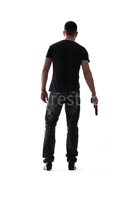 A semi-silhouette of a mystery man, from behind, with a gun – shot from low level.