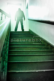 An atmospheric image of a hooded mystery man standing in a stairwell.