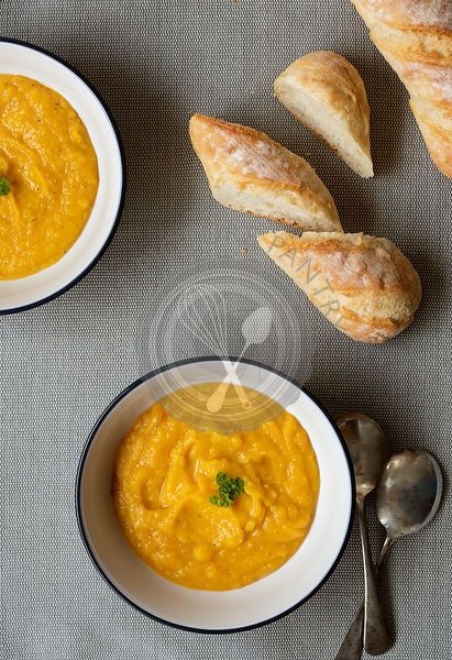 Two bowls of thick homemade pumpkin soup with two spoons and crusty bread.