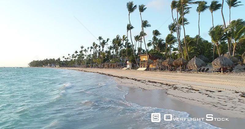 Tropical beach with palm trees. Flight over the sea low level early morning. Punta Cana, Dominican Republic