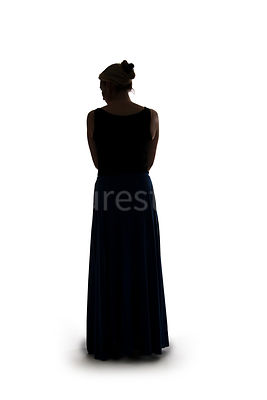 A silhouette of a woman in a long dress – shot from low level.
