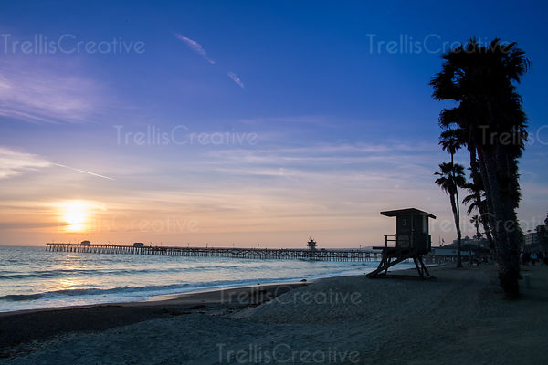 The shoreline with the pier and palm tree silouettes at sunset
