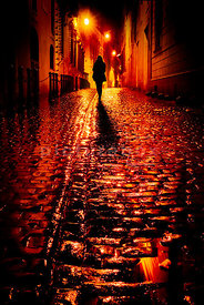 An atmospheric image of a lone woman walking down an empty cobbled street, at night time, in the rain in Rome, Italy