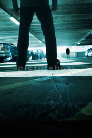 An atmospheric image of a man being followd by another man in a Dark car park.