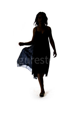 A silhouette of woman walking in a summer dress – shot from eye level.