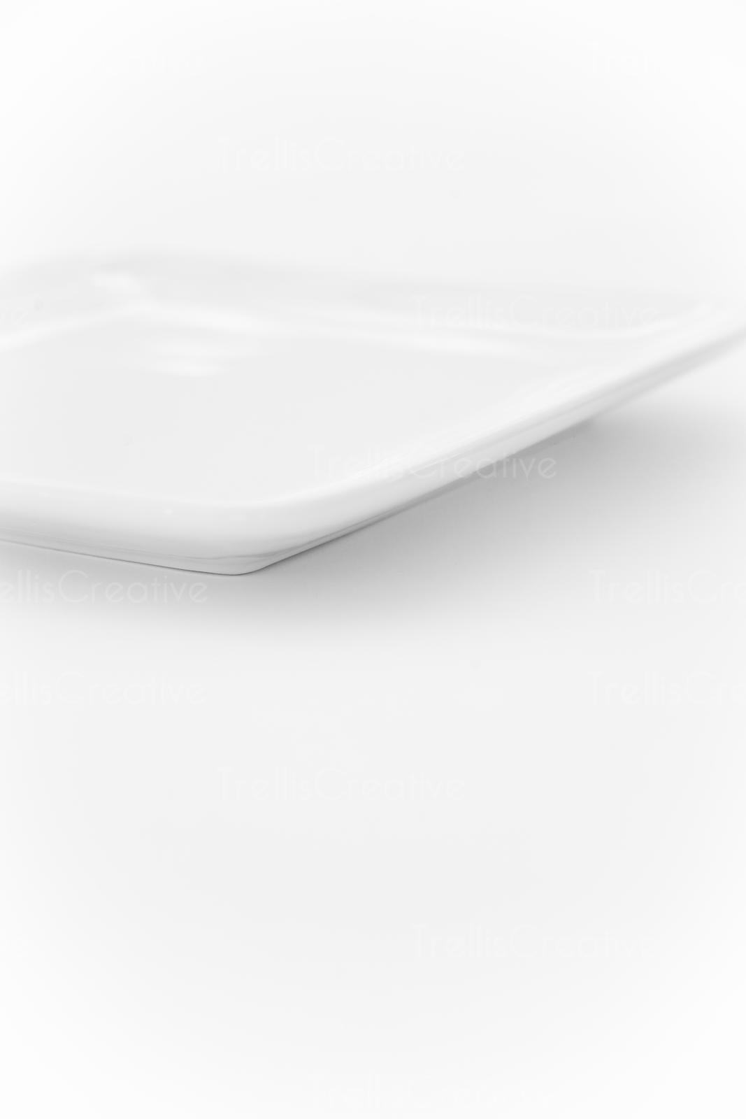 Empty white square dish on white background