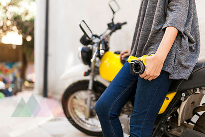 Close-up of woman with camera leaning against motorbike