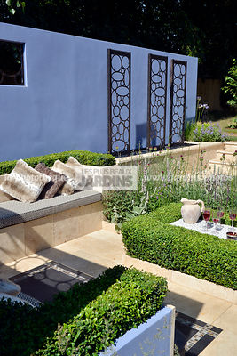 Terrasse contemporaine : coin repos, banquette, Buxus sempervirens (buis), Sculpture (Métal Design Furniture Ltd), Mur de cou...